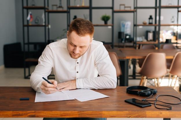 Талантливый молодой человек в повседневной одежде пишет ноты ручкой на листе бумаги