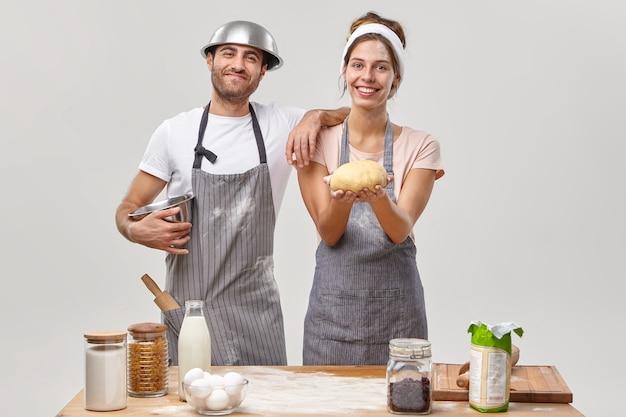 La talentuosa giovane donna cuoca ottiene molto nella sfera culinaria, tiene l'impasto crudo preparato, prova nuove ricette, uomo felice con una ciotola in testa, pronto ad aiutare con la cottura di torte o pasticcini. prodotti alimentari in giro