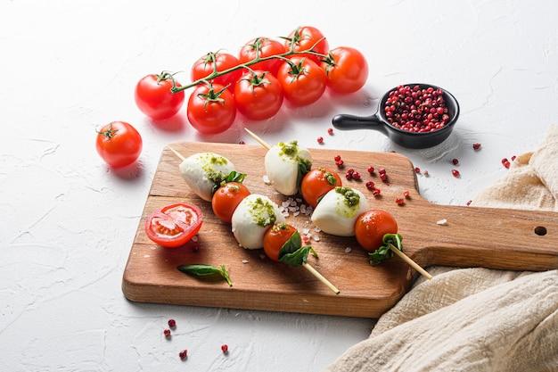タリアン料理-カプレーゼサラダ-トマト、モッツァレラチーズ、バジルの串焼き、ペストソース、古いまな板に地中海料理のコンセプト