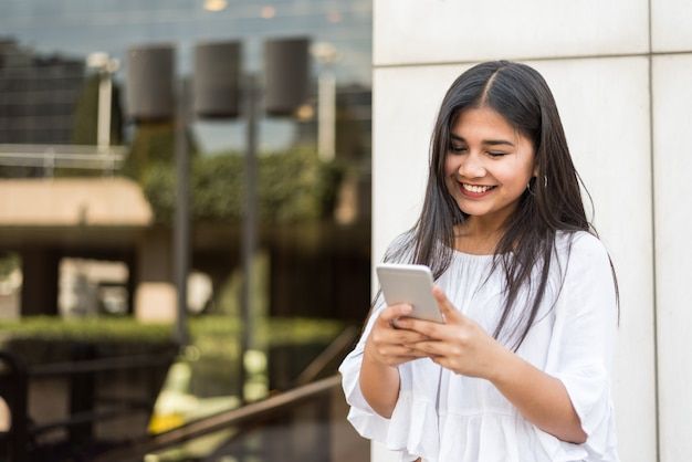 若い幸せな女性talikngと彼女の携帯電話でテキストメッセージ