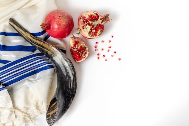 Talit, shofar, pomegranate and pomegranate seeds, top view