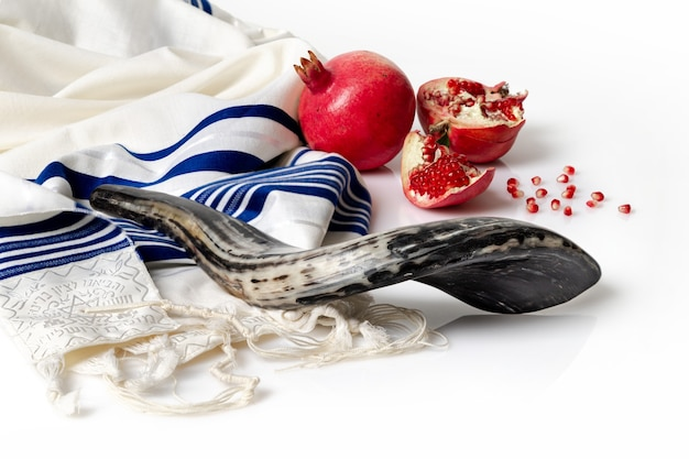 Talit, shofar, pomegranate and pomegranate seeds on wite table