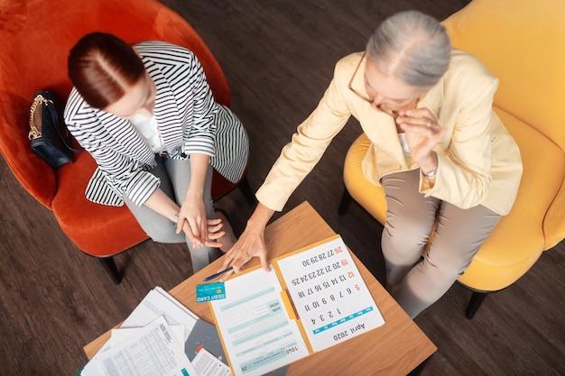 ビジネスを話します。計画カレンダーに寄りかかってテーブルで肘掛け椅子に座っている2人の白人ビジネス女性の上面図