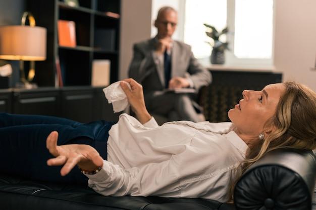 トークセラピー。治療セッション中にソファに横になり、医師と話している40代の深刻な女性