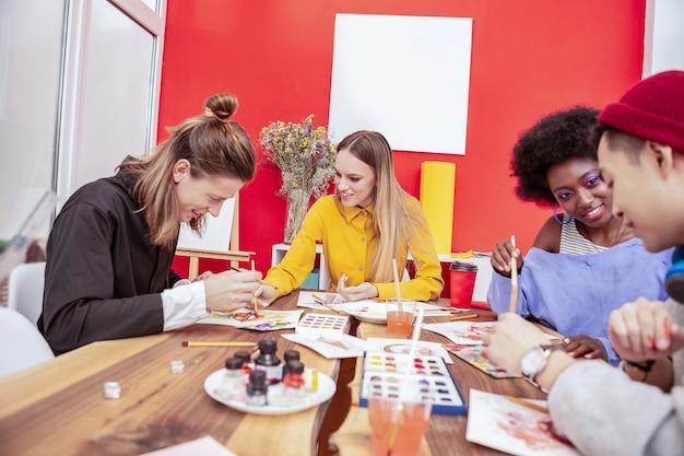 グループメイトと話してください。彼女のグループメートと話している黄色のドレスを着ているブロンドの髪の芸術学生