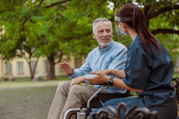 で彼の看護師と会話をしている車椅子で患者を回復しているおしゃべりな老人