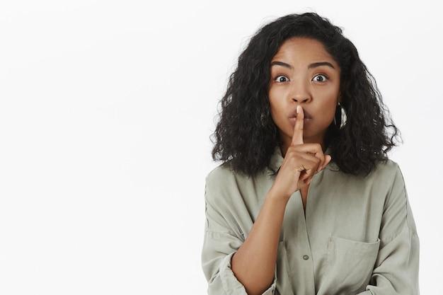 Разговорчивая привлекательная афроамериканка в модной рубашке с кудрявой прической, распространяющая сплетни
