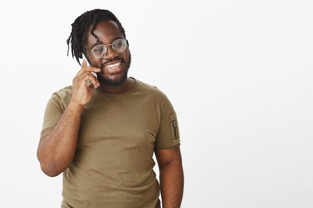 彼の電話で白い壁にポーズをとって眼鏡をかけたおしゃべりな男