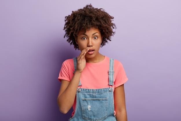 おしゃべりな印象の暗い肌の女性は、口の近くに手を保ち、衝撃的なゴシップを伝え、ひどい噂を共有します