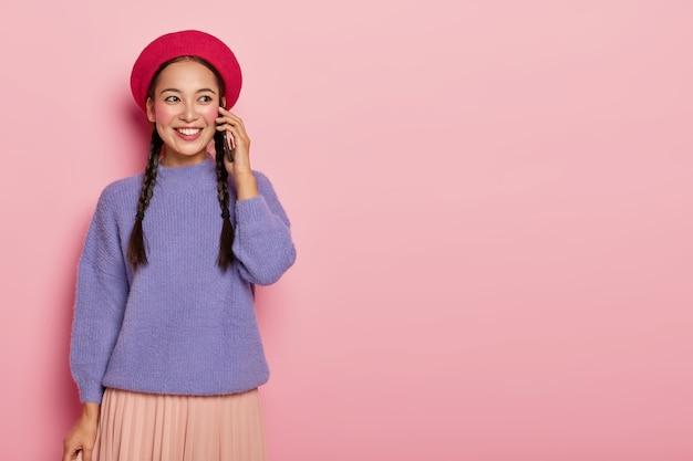 동부 외모의 수다스러운 예쁜 소녀는 전화 통화를 즐기고 귀 근처에 현대적인 휴대 전화를 들고 세련된 빨간색 베레모와 보라색 점퍼를 입습니다.