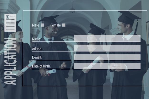 明るい未来について話します。大学の廊下を歩いて話している卒業式のガウンの4人の大学卒業生