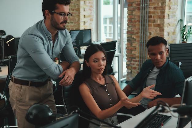 Разговор о бизнес-многонациональной группе молодых людей, смотрящих на монитор компьютера и обсуждающих
