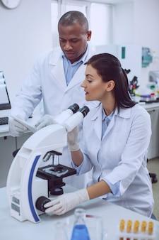 프로젝트에 대해 이야기합니다. 현미경으로 작업하고 동료와 작업에 대해 논의하는 숙련 된 과학자 결정