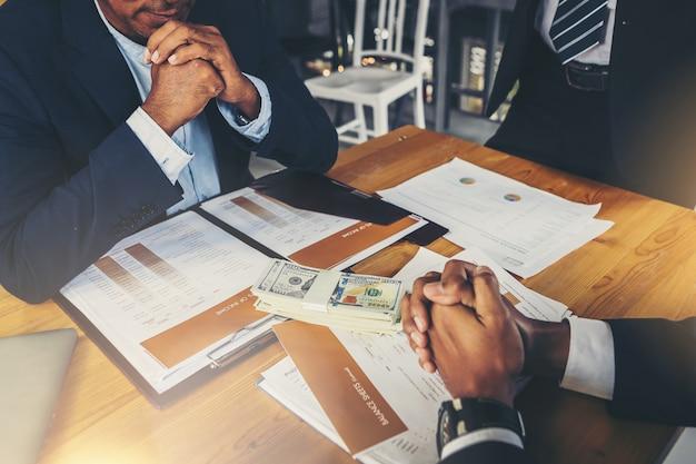 深刻なビジネスについて話しています。手を繋いでいる思慮深いビジネス人々は、彼の職場に座ってビジネスパートナーを探しています。
