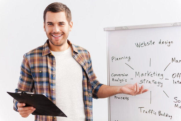 Кстати о стратегии. уверенный молодой человек в элегантной повседневной одежде, стоящий возле доски и указывая на нее с улыбкой