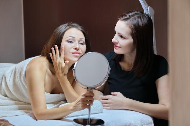 美容サロンの鏡で話していると笑顔の女性美容師と成熟した女性患者