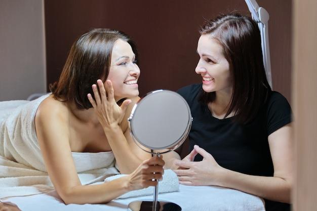 Говорящая и улыбающаяся женщина-косметолог и зрелая пациентка с зеркалом в салоне красоты