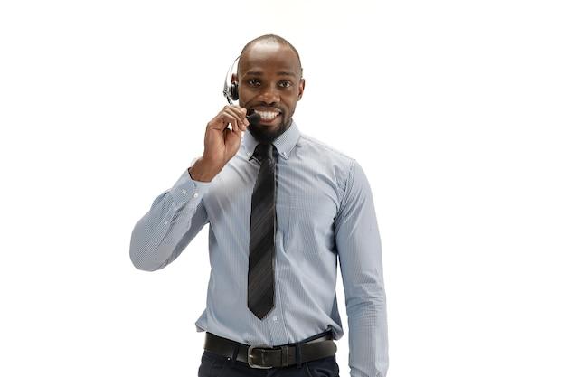 말하고 웃고. 흰색 스튜디오 배경에 헤드셋이 있는 젊은 아프리카계 미국인 콜 센터 컨설턴트. 광고, 텍스트에 대 한 copyspace입니다. 전문 직업, 작업, 직업, 의사 소통의 개념.