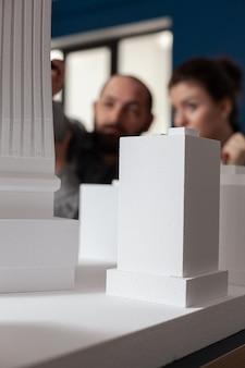 전문 사무실에서 책상에 앉아 말하는 건축가 팀