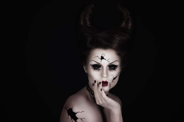 Talking broken doll with horns on her head
