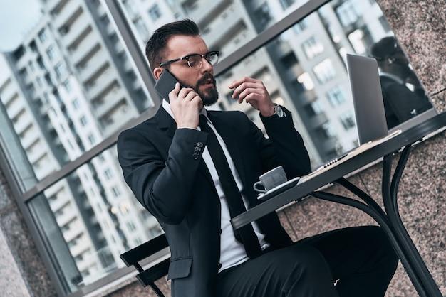 Обсуждение деловых подробностей. красивый молодой человек в полном костюме разговаривает по своему смартфону