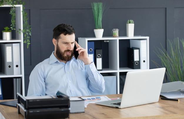 ビジネスの詳細を話します。オフィスの机に座っている間電話で話しているハンサムな若い男