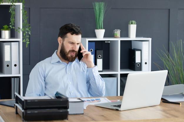 Обсуждение деловых подробностей. красивый молодой человек разговаривает по телефону, сидя за офисным столом
