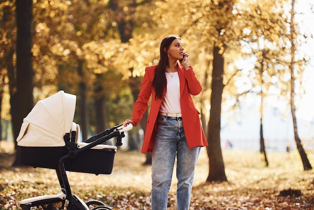 Talking by the phone. mother in red coat have a walk with her kid in the pram in the park at autumn time.