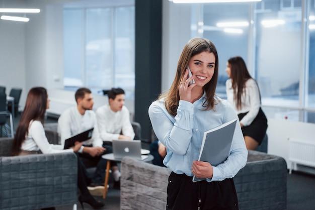 電話で話します。バックグラウンドで従業員とオフィスに立っている若い女の子の肖像画