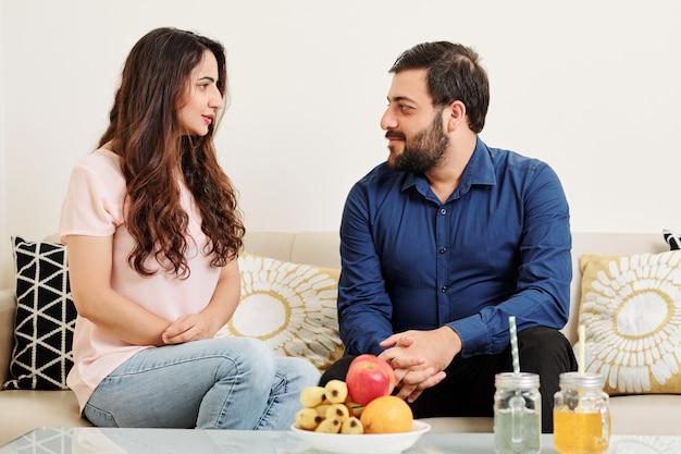 Talking couple resting on sofa
