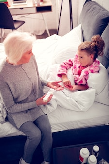 Talking to granny. granddaughter feeling sad and sick while lying in bed and talking to granny giving her medicine