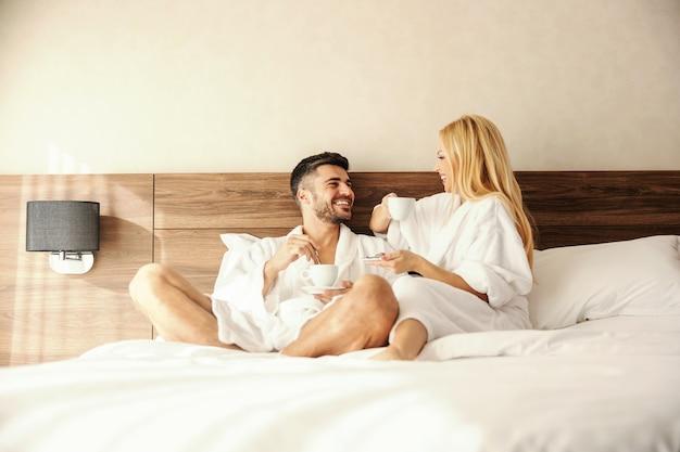 Разговор в постели, утренняя вечеринка сплетен с любимым человеком за чашкой горячего напитка, кофе или чая