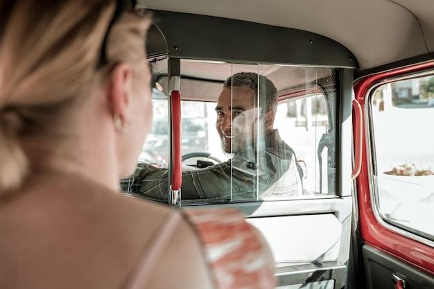 차에서 이야기. 차를 운전하고 뒷좌석에 앉아 있는 아내를 창밖으로 바라보는 웃는 남자.
