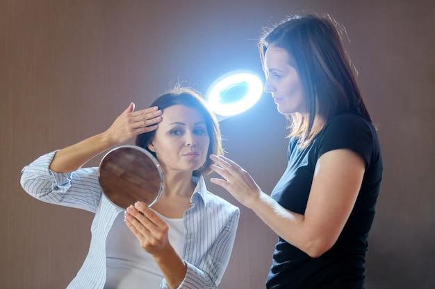 Говорящая зрелая пациентка с зеркалом в салоне красоты