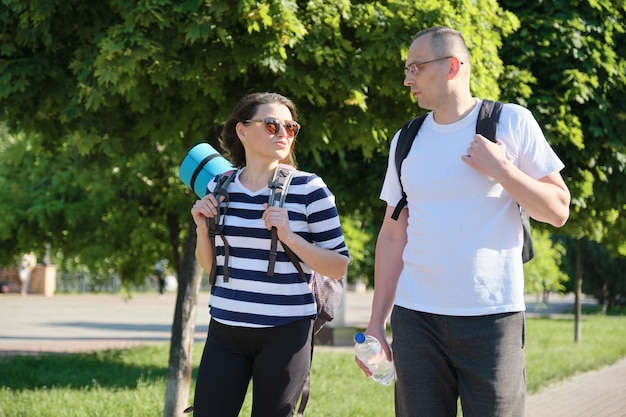 Talking middle-aged man and woman, couple walking along park road for sports fitness training