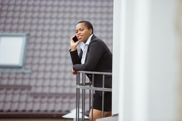 電話で話すオフィスの服装でアフリカ系アメリカ人の実業家の笑顔