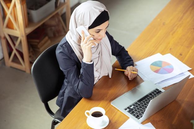 전화 통화, 주의를 기울였습니다. 오픈스페이스나 사무실에서 일하는 동안 히잡을 쓴 아름다운 아라비아 여성 사업가. 직업의 개념, 비즈니스 영역의 자유, 리더십, 성공, 현대적인 솔루션.