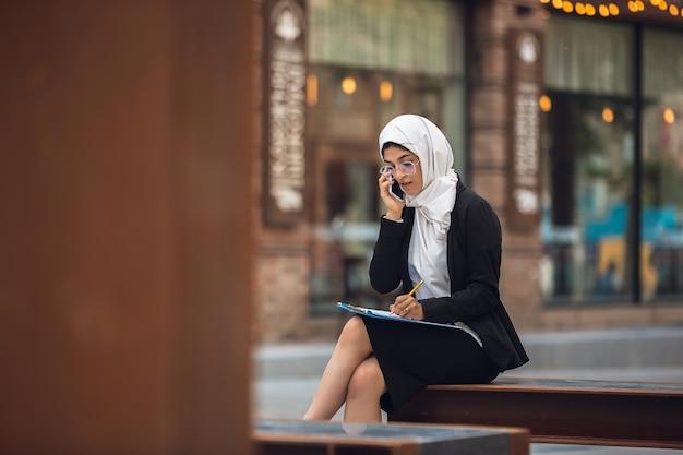 電話で話します。美しいイスラム教徒の成功した実業家の肖像画