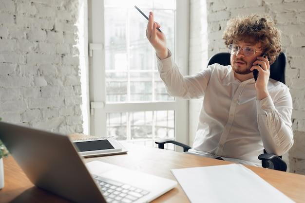 電話で話しています。オフィスで働くビジネス服装の白人の若い男