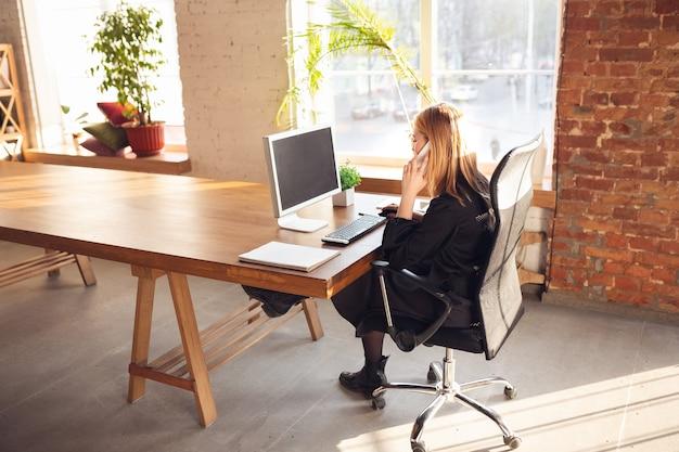 電話で話しています。オフィスで働くビジネス服装の白人の若い女性