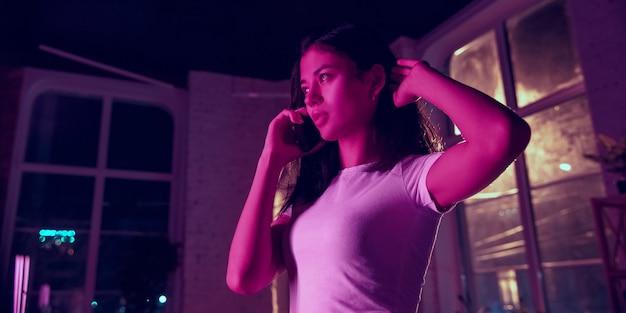 전화 통화 중. 네온 조명이 켜진 실내에서 잘생긴 세련된 여성의 영화적 초상화. 보라색 - 파란색의 영화 효과처럼 톤. 실내에서 화려한 조명으로 스마트폰을 사용하는 백인 모델입니다. 전단.
