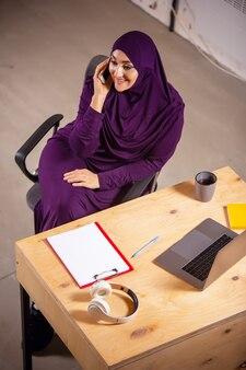 電話で話します。オンラインレッスン中に自宅で幸せなイスラム教徒の女性。現代のテクノロジー、遠隔教育、民族性、伝統の概念。人間の感情、ライフスタイル。自宅に座っているラップトップを使用します。
