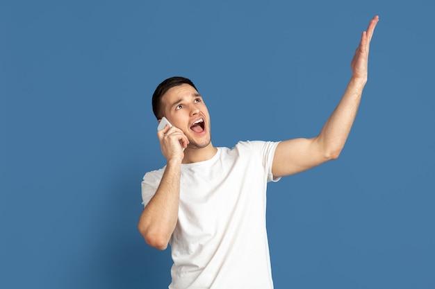 電話で話している、指さしている。ブルー スタジオの背景に白人の若い男の肖像画。パステル カラーのカジュアル スタイルの美しい男性モデル。人間の感情、表情、販売のコンセプト。