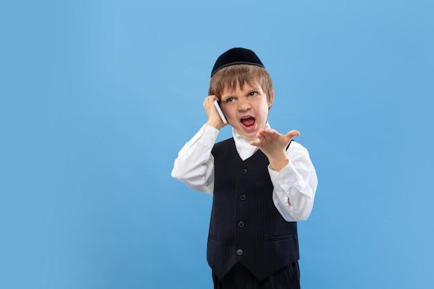電話で話します。青い壁に隔離された若い正統派ユダヤ人の少年の肖像画。プリム、ビジネス、お祭り、休日、子供時代、お祝いのペサッハまたは過越の祭り、ユダヤ教、宗教の概念。