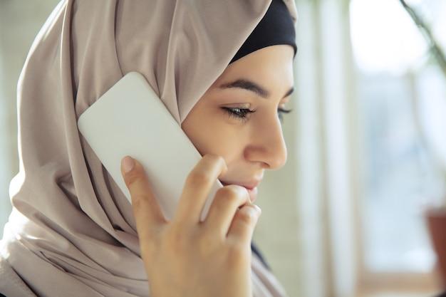 전화 통화, 미소. 오픈스페이스나 사무실에서 일하는 동안 히잡을 쓴 아름다운 아라비아 여성 사업가의 초상화를 클로즈업하세요. 직업, 리더십, 성공, 현대적인 솔루션의 개념.