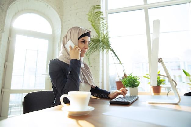 커피를 마시면서 전화통화를 합니다. 오픈스페이스나 사무실에서 일하는 동안 히잡을 쓴 아름다운 아라비아 여성 사업가의 초상화. 직업, 리더십, 성공, 현대적인 솔루션의 개념.