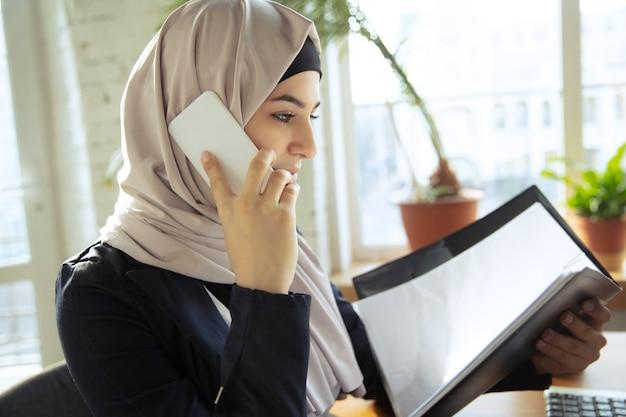문서를 검토하는 동안 전화 통화. 오픈스페이스나 사무실에서 일하는 동안 히잡을 쓴 아름다운 아라비아 여성 사업가. 직업의 개념, 비즈니스 영역의 자유, 성공, 현대적인 솔루션.