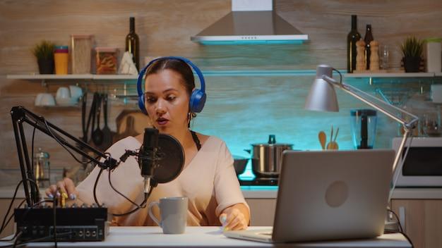부엌에서 브이로그 녹화를 하는 동안 전문 마이크에 대해 이야기합니다. 온에어 온라인 제작 인터넷 방송 쇼 호스트 스트리밍 라이브 콘텐츠, 디지털 소셜 미디어 커뮤니케이션 녹음