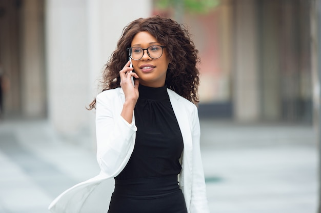 Talking phone. african-american businesswoman in office attire smiling, looks confident and serious, busy. finance, business, equality and human rights concept. beautiful young model, successful.