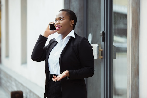 Talking on phone africanamerican businesswoman in office attire smiling looks confident